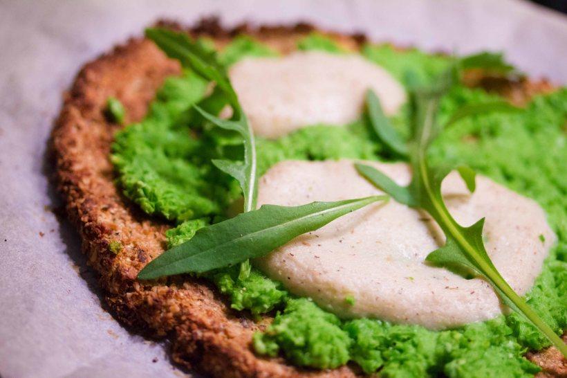 Grüne Pizza mit einem Boden aus Blumenkohl und Mozzarella aus Cashews und Flohsamenschalen